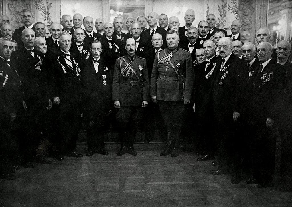Н.В. Цар Борис ІІІ с генерал Христо Луков (дясно) и запасните генерали Никола Жеков и Владимир Вазов (ляво) и други военни и политически лица на церемония в Двореца, 1935-1937 г. Зад тях на стълбите - учителите на Царя от дворцовата гимназия